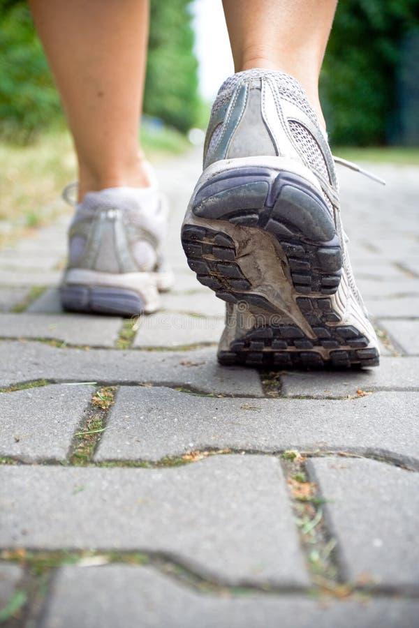 La donna che cammina, mette in mostra i pattini correnti immagine stock