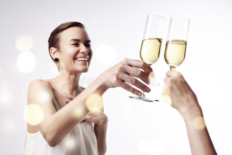 La donna che celebra e dice l'acclamazioni al partito con un vetro di champagne Risuoni insieme i vetri immagini stock libere da diritti