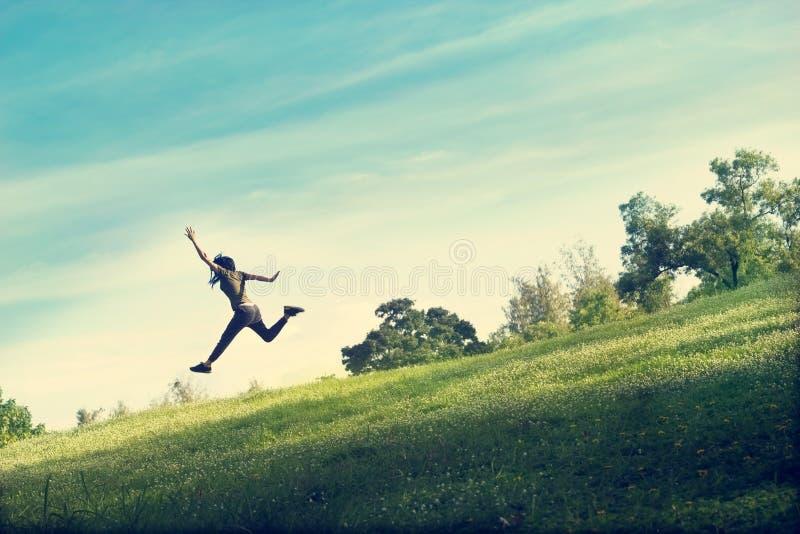 La donna che corre e che salta divertente si rilassa su erba verde e sul fiore fotografia stock