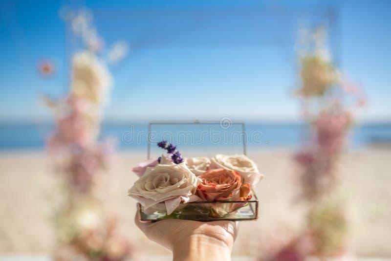 La donna che del primo piano le mani tengono la scatola di vetro per le fedi nuziali ha decorato con i fiori e il banch rosa fres immagini stock libere da diritti