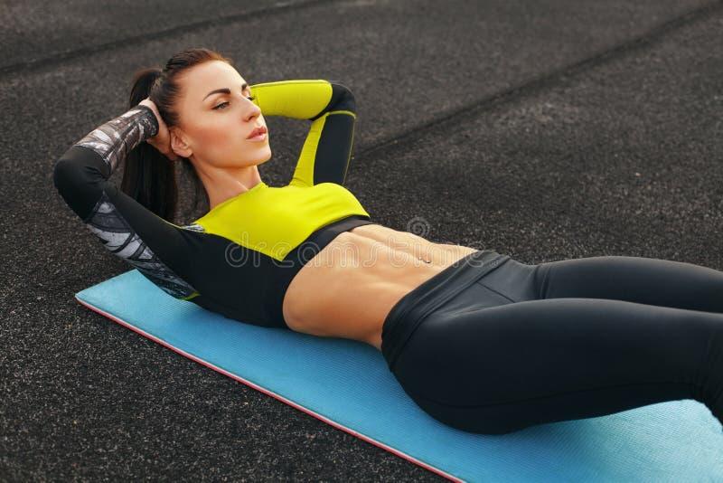 La donna che di forma fisica fare si siede aumenta nel risolvere dello stadio Ragazza sportiva che esercita i abdominals, all'ape immagine stock libera da diritti