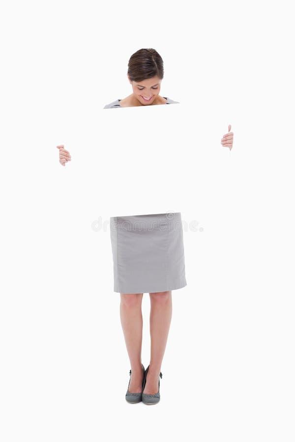La donna che esamina giù in bianco firma dentro le sue mani fotografia stock libera da diritti