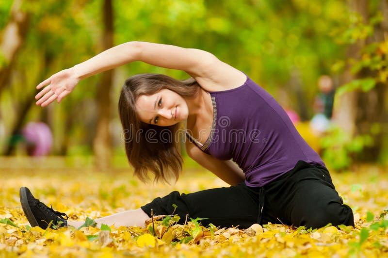 La donna che fa l'yoga si esercita nella sosta di autunno fotografia stock libera da diritti