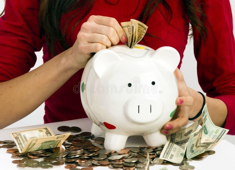 La donna che farcisce la valuta degli Stati Uniti conia il risparmio dei contanti del porcellino salvadanaio fotografia stock