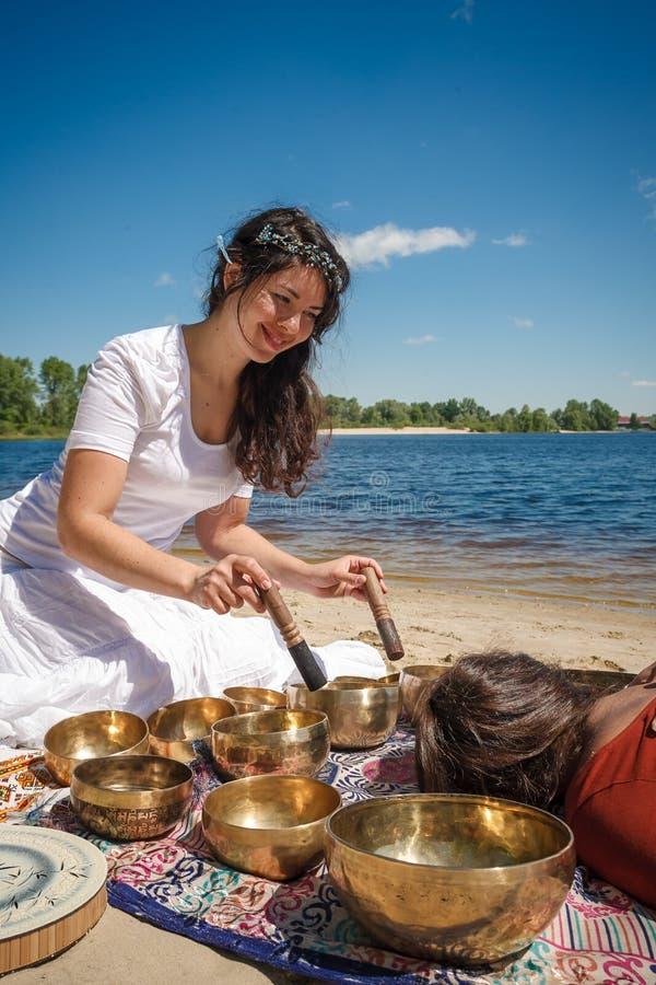 La donna che gioca un canto lancia anche conosciuto come ciotole tibetane di canto, ciotole himalayane Fabbricazione del massaggi immagine stock libera da diritti