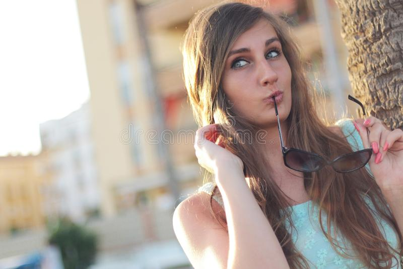 La Donna Che Indossa Il Nero Di Teal Floral Tank Top Holding Ha Incorniciato Gli Occhiali Da Sole Vicino All'albero Che Posa Per Dominio Pubblico Gratuito Cc0 Immagine