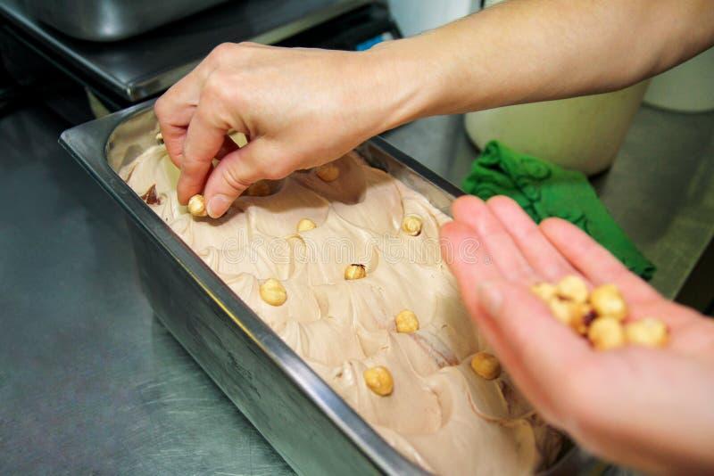 La donna che lavora alla fabbrica del gelato è decora del gelato cremoso dei sapori della nocciola con i pezzi, i bei pezzi e la  immagini stock
