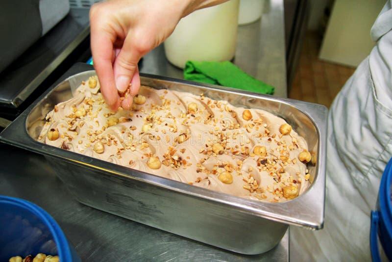 La donna che lavora alla fabbrica del gelato è decora del gelato cremoso dei sapori della nocciola con i pezzi, i bei pezzi e la  immagine stock