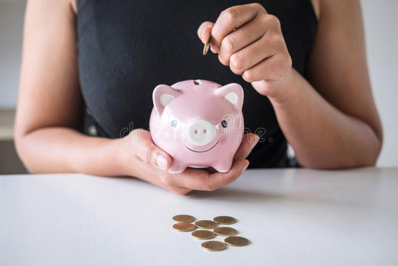 La donna che mette la moneta dorata nel porcellino salvadanaio rosa per aumenta l'affare crescente al profitto ed il risparmio co immagini stock