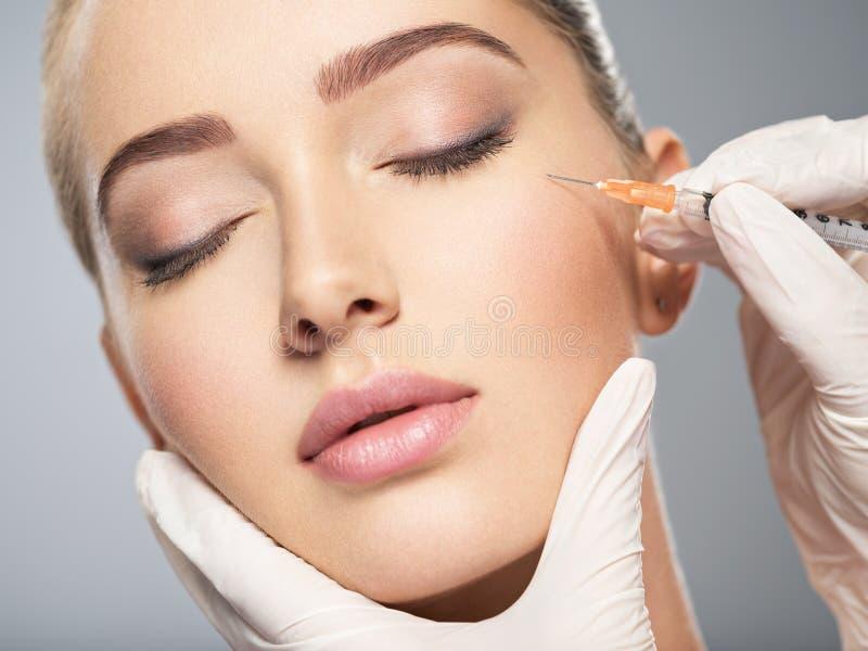 La donna che ottiene l'iniezione cosmetica di botox vicino osserva fotografia stock