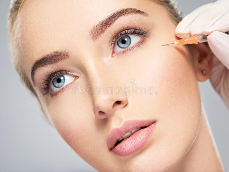 La donna che ottiene l'iniezione cosmetica di botox vicino osserva immagini stock libere da diritti