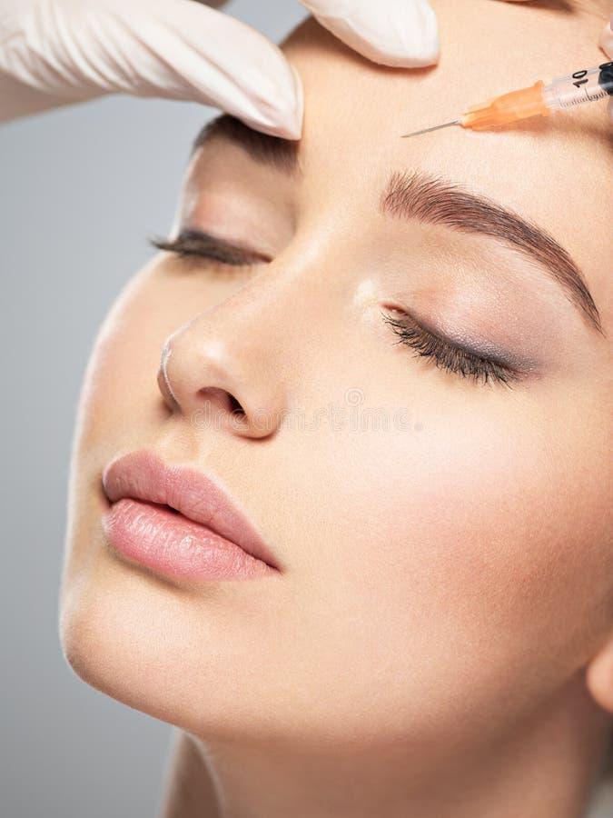 La donna che ottiene l'iniezione cosmetica di botox vicino osserva immagini stock