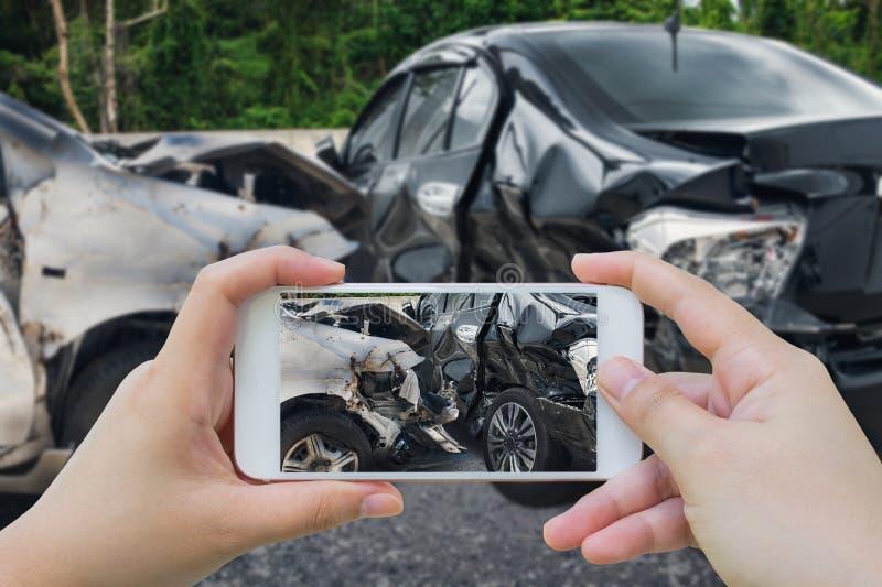 La donna che per mezzo dello smartphone prende la foto dell'incidente di incidente stradale fotografie stock