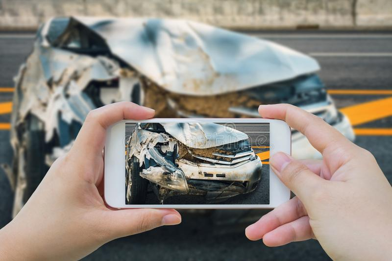 La donna che per mezzo dello smartphone prende la foto dell'incidente di incidente stradale immagine stock
