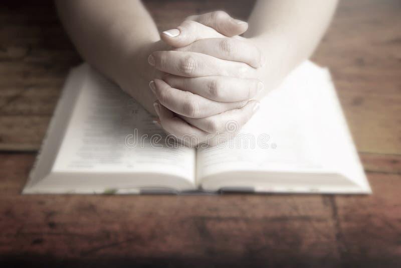 La donna che prega con le sue mani ha ripiegato la sua bibbia fotografia stock libera da diritti