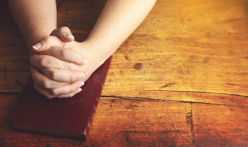 La donna che prega con le sue mani ha ripiegato la sua bibbia immagini stock libere da diritti