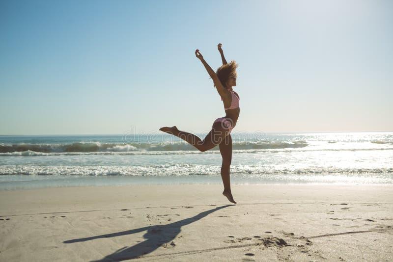 La donna che salta alla spiaggia un giorno soleggiato fotografie stock libere da diritti