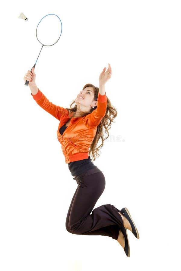 La donna che salta con la racchetta per il volano di cattura di volano fotografia stock