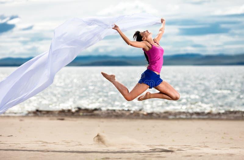 La donna che salta sulla spiaggia con un tessuto bianco fotografia stock