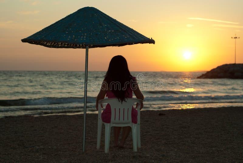 La donna che si siede sulla presidenza ed ammira il tramonto fotografia stock