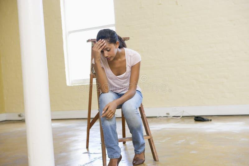 La donna che si siede sulla scaletta nello spazio vuoto sembra faticosa fotografia stock libera da diritti