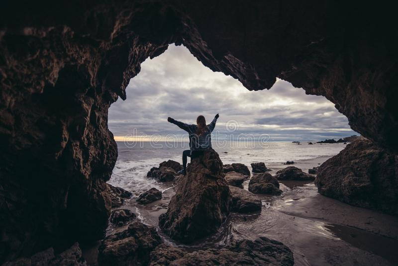 La donna che si siede sulle rocce dell'oceano scava con le armi alzate e gode della natura e della libertà fotografie stock