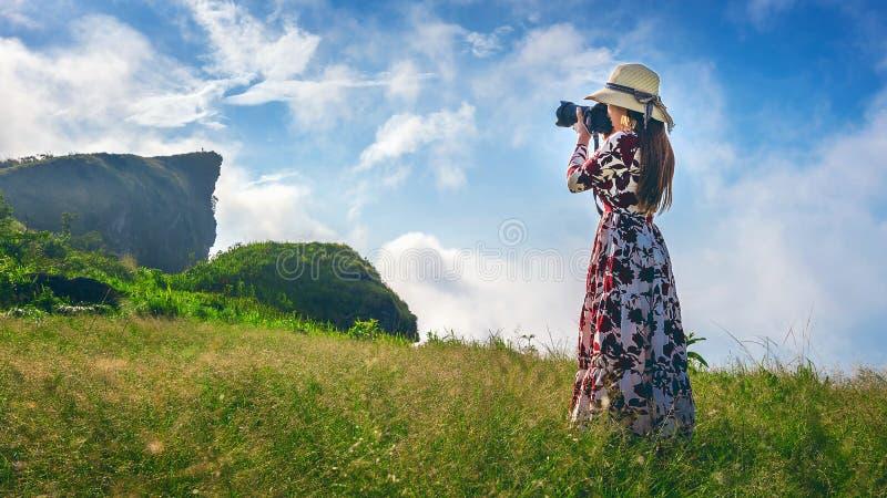 La donna che sta sul prato e che tiene la macchina fotografica prende la foto alle montagne di Fa di 'chi' di Phu in Chiangrai, T immagini stock
