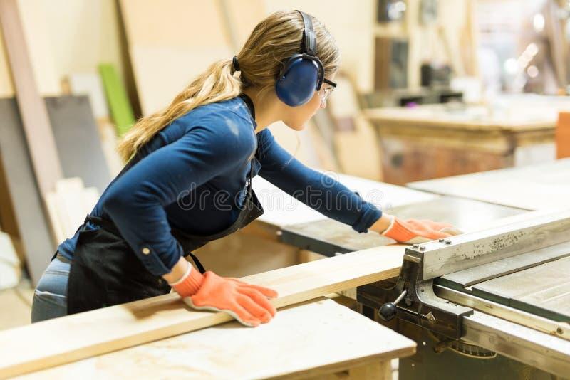 La donna che taglia un certo legno con una tavola ha visto fotografie stock libere da diritti