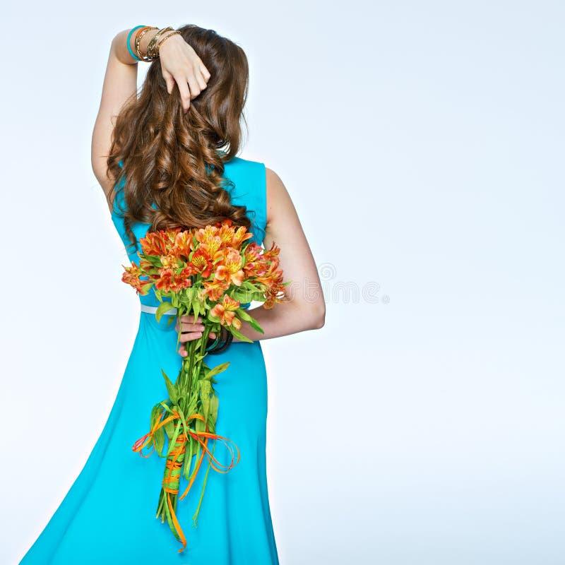 La donna che la tenuta fiorisce il mazzo ha girato suo indietro e hai commovente fotografia stock