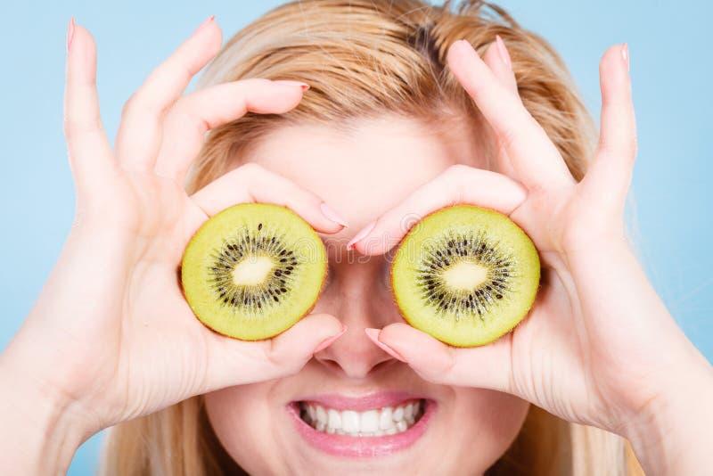 La donna che tiene il kiwi verde gradisce gli occhiali immagini stock