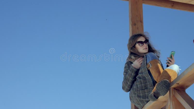 La donna che usando Smartphone si rilassa sul banco in bello parco Giovane donna nella fabbricazione dei gesti sull'esposizione d fotografia stock