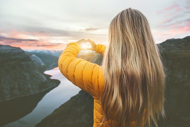 La donna che viaggia in montagne del tramonto passa il simbolo del cuore a forma di fotografie stock