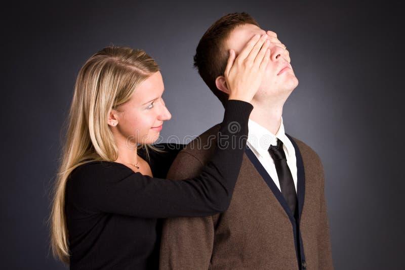 La donna chiude le mani dietro un occhio degli uomini. fotografia stock libera da diritti