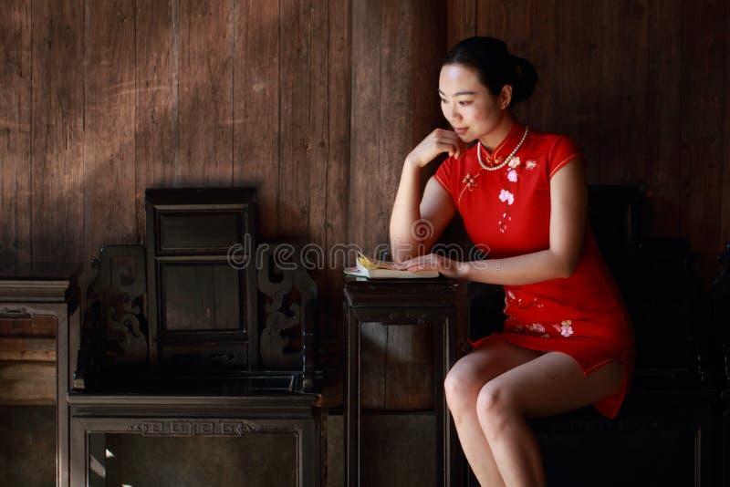 La donna cinese felice nel cheongsam rosso ha letto il libro immagini stock libere da diritti