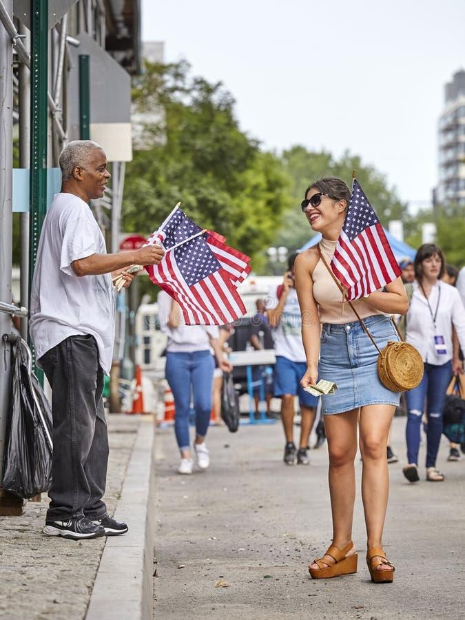 La donna compra la bandiera americana durante la festa dell'indipendenza immagini stock