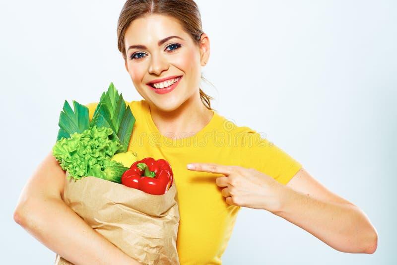 La donna con alimento verde indica un dito al prodotto immagini stock