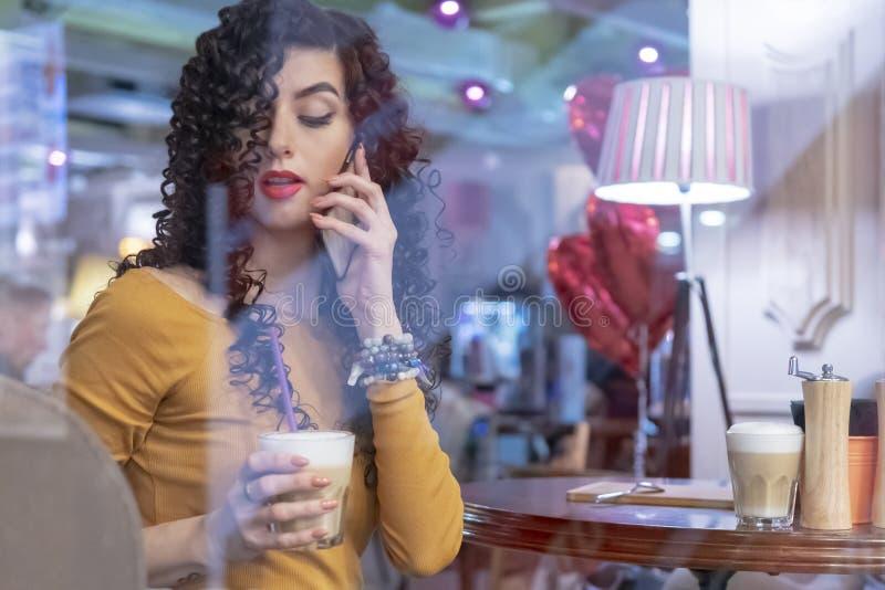 La donna con caffè parla dal telefono fotografia stock libera da diritti