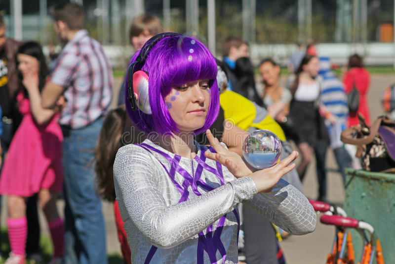 La donna con capelli porpora mostra un trucco con una palla di vetro in VDNH a Mosca immagine stock libera da diritti