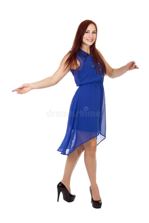 La donna con capelli rossi balla in suo vestito blu. immagine stock
