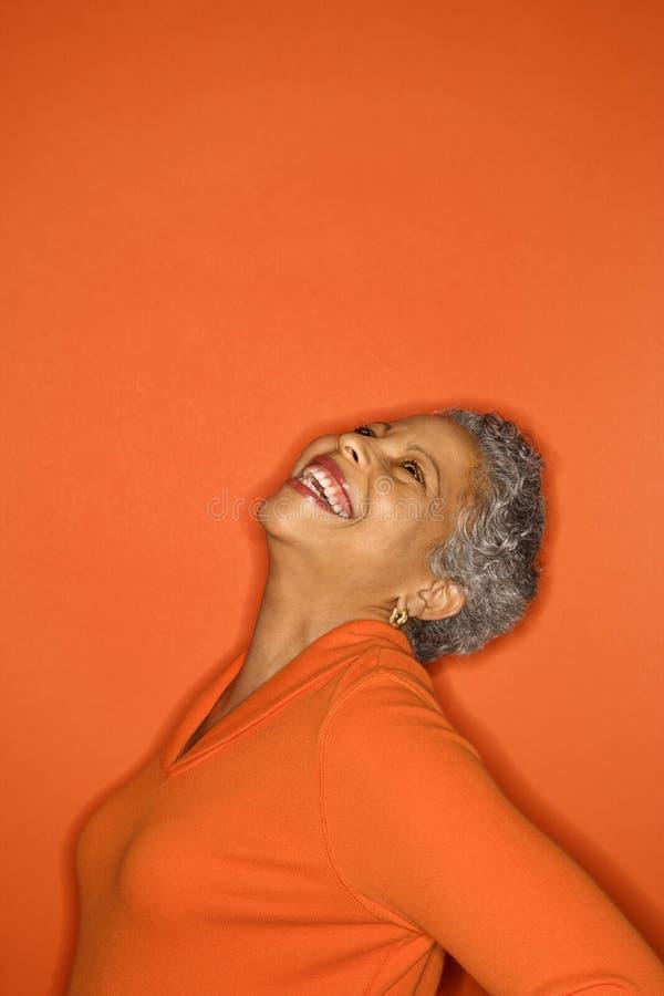 La donna con dirige indietro sorridere. immagini stock