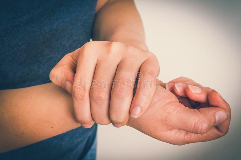 La donna con dolore del polso sta tenendo la sua mano facente male immagini stock