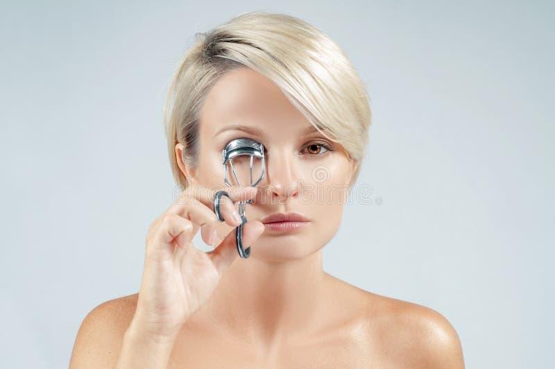 la donna con il bastone Bella donna che per mezzo dei cigli d'arricciatura del bigodino del ciglio fotografia stock