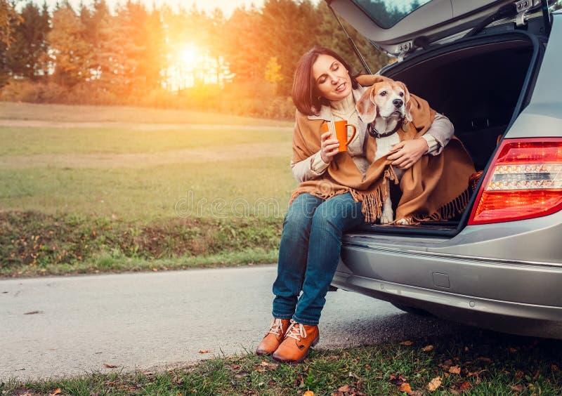 La donna con il cane si siede insieme in camion del gatto e riscalda il tè caldo fotografia stock libera da diritti