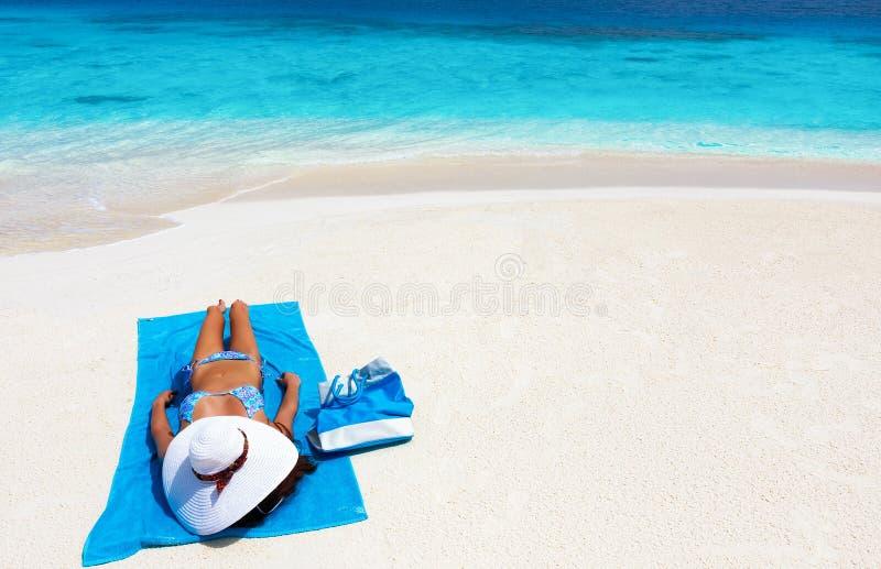 La donna con il cappellino da sole si rilassa su una spiaggia tropicale immagine stock libera da diritti