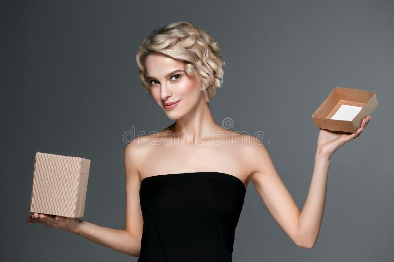 La donna con il contenitore di regalo dentro consegna il fondo grigio immagini stock