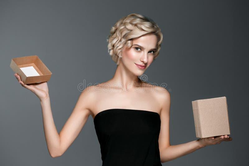 La donna con il contenitore di regalo dentro consegna il fondo grigio fotografie stock libere da diritti
