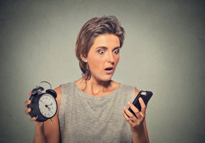 La donna con il telefono cellulare e la sveglia ha sollecitato tardi il funzionamento immagini stock libere da diritti