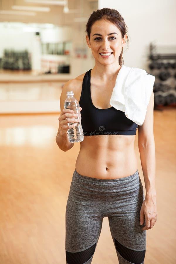 La donna con l'ABS tonificato che prende un'acqua si rompe immagine stock