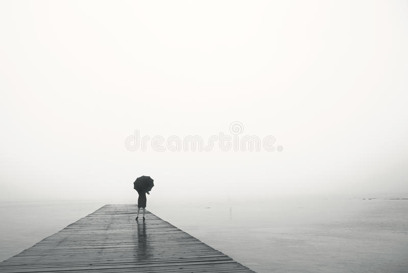 La donna con l'ombrello contempla pacificamente davanti al mare fotografia stock libera da diritti