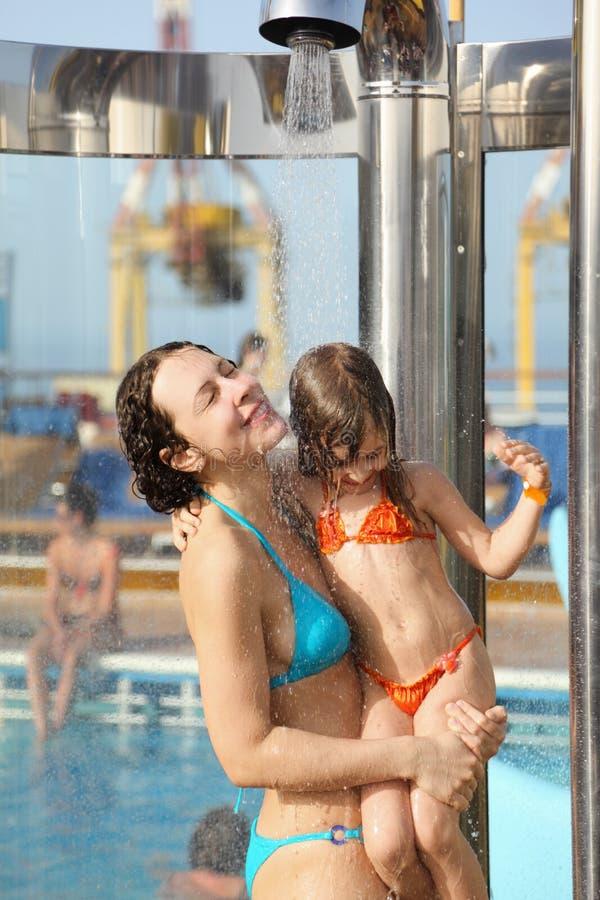 La donna con la figlia sta catturando un acquazzone fotografia stock libera da diritti